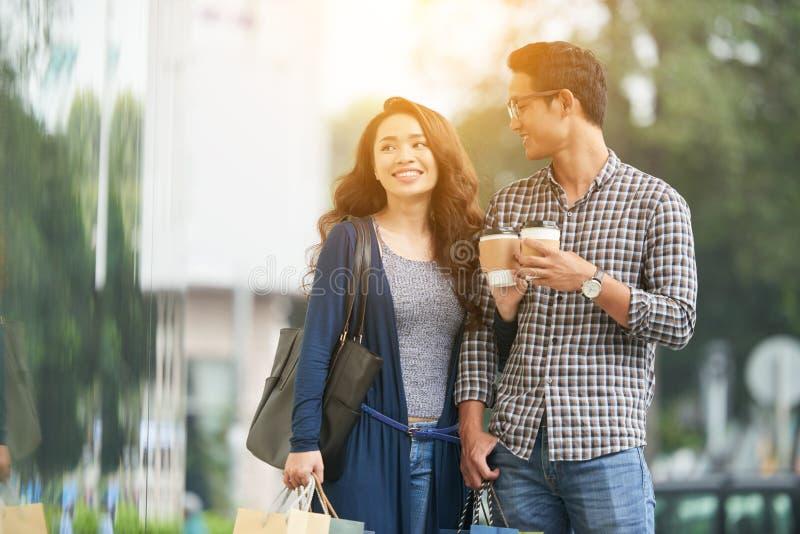 Pares felizes com café e sacos de compras imagem de stock royalty free
