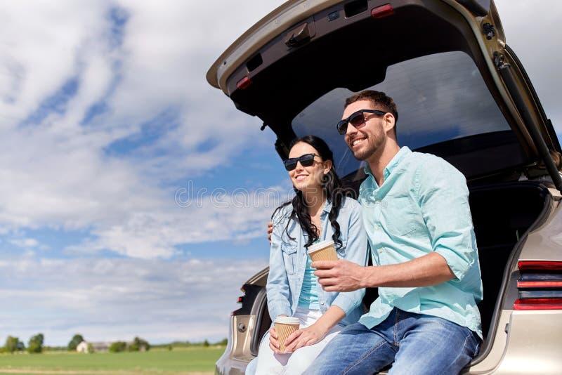 Pares felizes com café no tronco de carro do carro com porta traseira imagem de stock