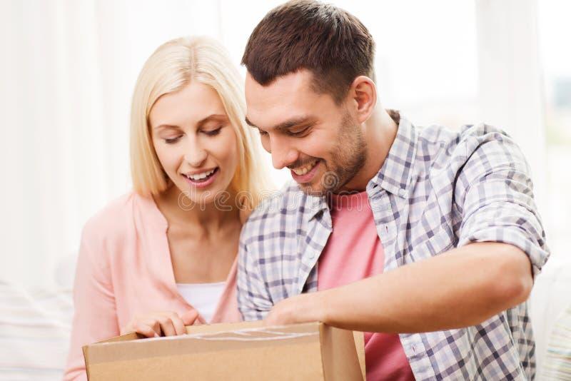 Pares felizes com caixa do pacote em casa fotografia de stock