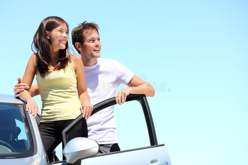 Pares felizes com carro