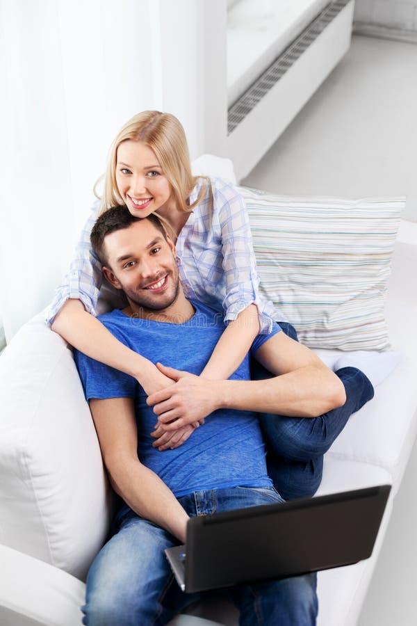 Pares felizes com computador portátil em casa imagem de stock