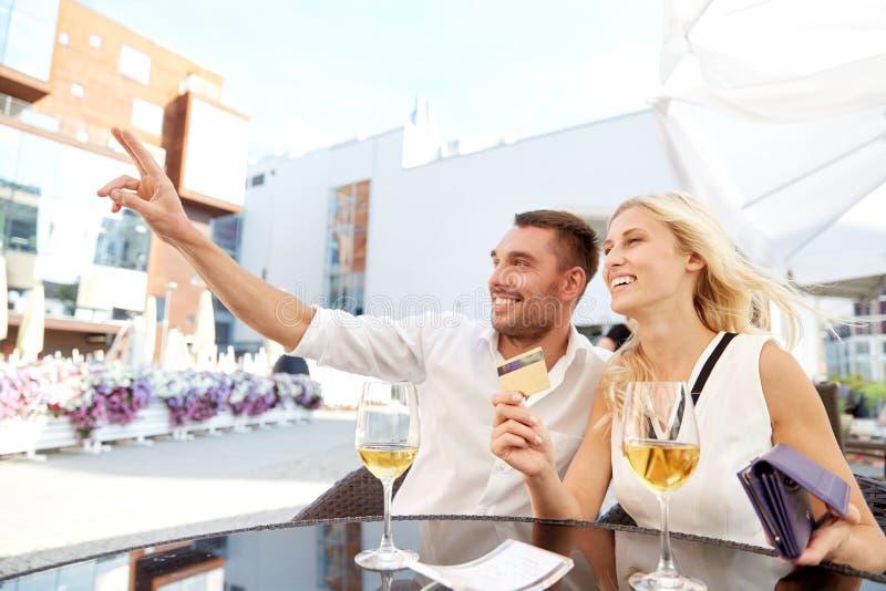 Pares felizes com conta pagando da carteira no restaurante fotografia de stock royalty free