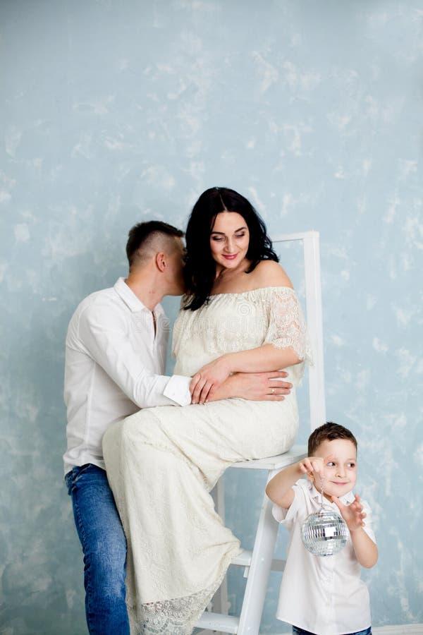 Pares felizes com a mulher gravida e a criança que levantam no estúdio fotografia de stock