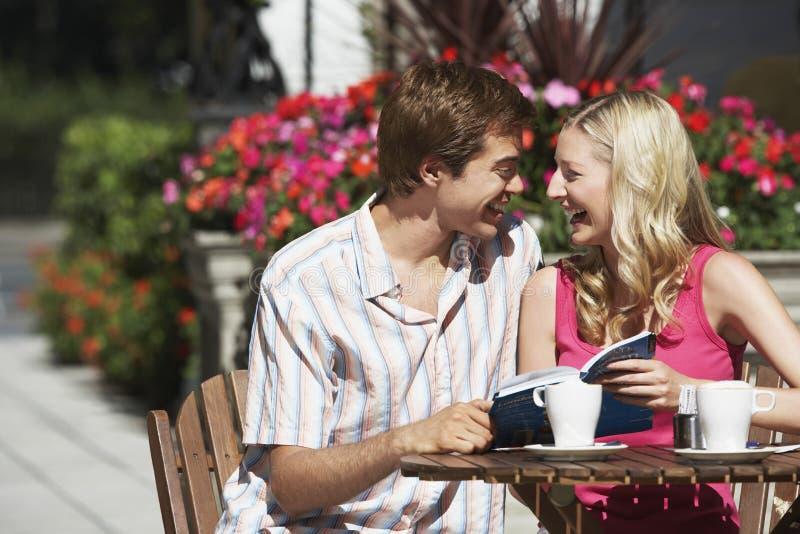 Pares felizes com o guia que senta-se no café exterior imagem de stock