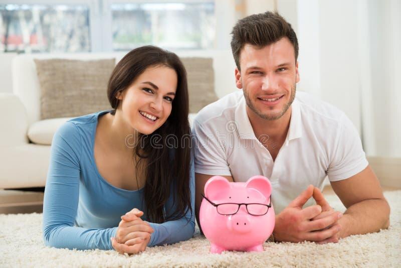 Pares felizes com o piggybank que encontra-se no tapete imagem de stock