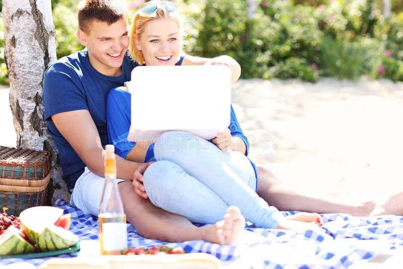 Pares felizes com o portátil na praia fotos de stock