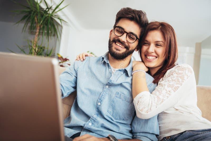 Pares felizes com o portátil que passa o tempo junto imagem de stock royalty free