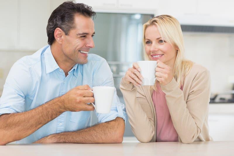 Pares felizes com os copos de café na cozinha fotos de stock royalty free