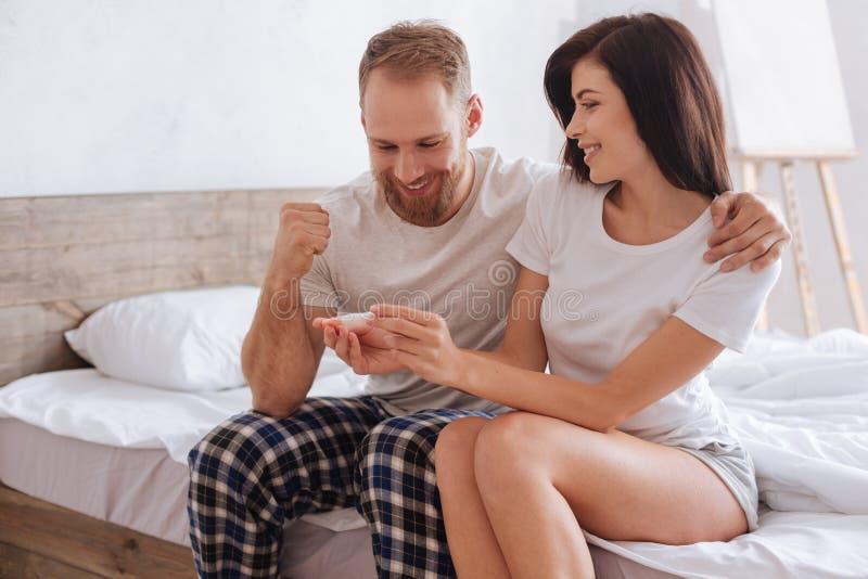 Pares felizes com resultados do teste de gravidez fotos de stock