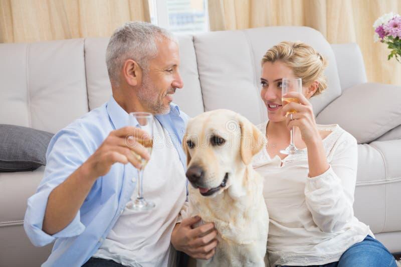 Pares felizes com seu champanhe bebendo do cão de estimação fotografia de stock