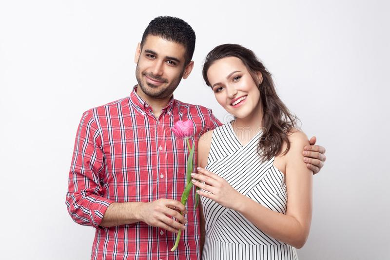 Pares felizes com tulipa, sorrindo, abraçando e olhando a câmera Retrato do homem considerável na camisa quadriculado vermelha e  imagens de stock