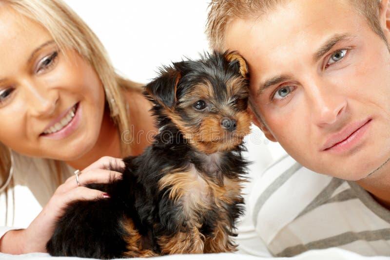 Pares felizes com um filhote de cachorro foto de stock royalty free