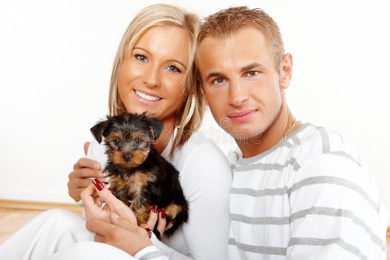 Pares felizes com um filhote de cachorro fotos de stock royalty free
