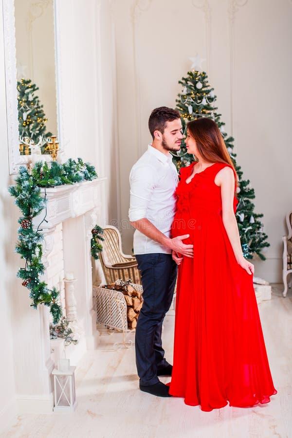 Pares felizes da família no Natal na chaminé Beijo e aperto felizes dos pares Sala de visitas decorada pela árvore do Xmas imagem de stock royalty free