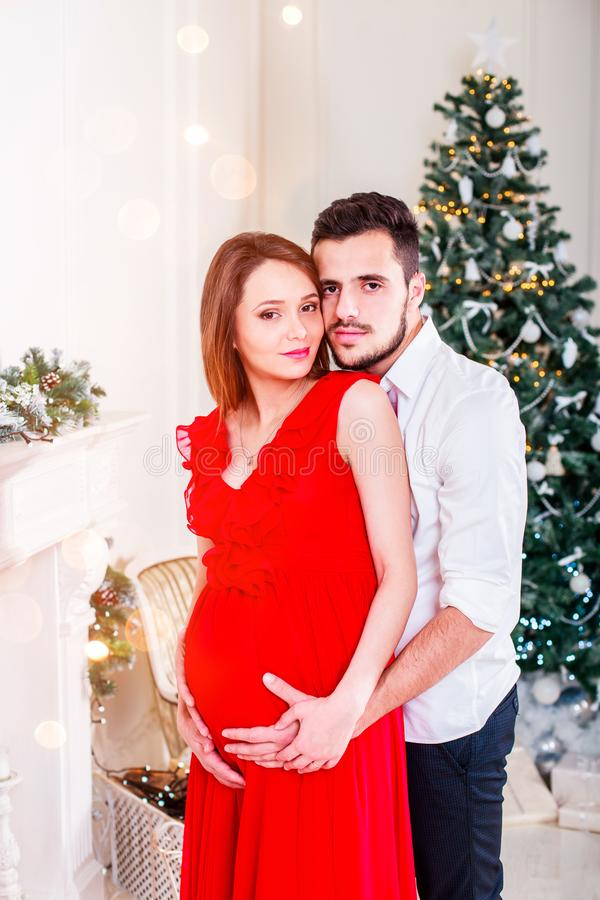 Pares felizes da família no Natal na chaminé Sala de visitas decorada pela árvore do Xmas e pela caixa de presente atual fotos de stock