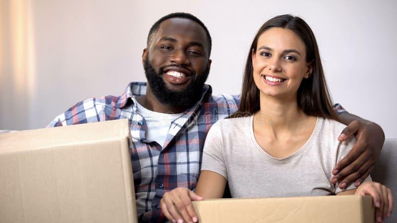 Pares felizes da misturado-raça que guardam as caixas da caixa, prontas para mover-se no apartamento novo fotos de stock