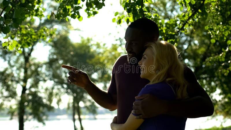 Pares felizes da raça misturada que abraçam e que apreciam a vista bonita no rio no parque foto de stock
