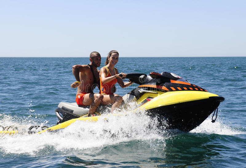 Pares felizes das salvas-vidas em um 'trotinette' da água fotos de stock royalty free