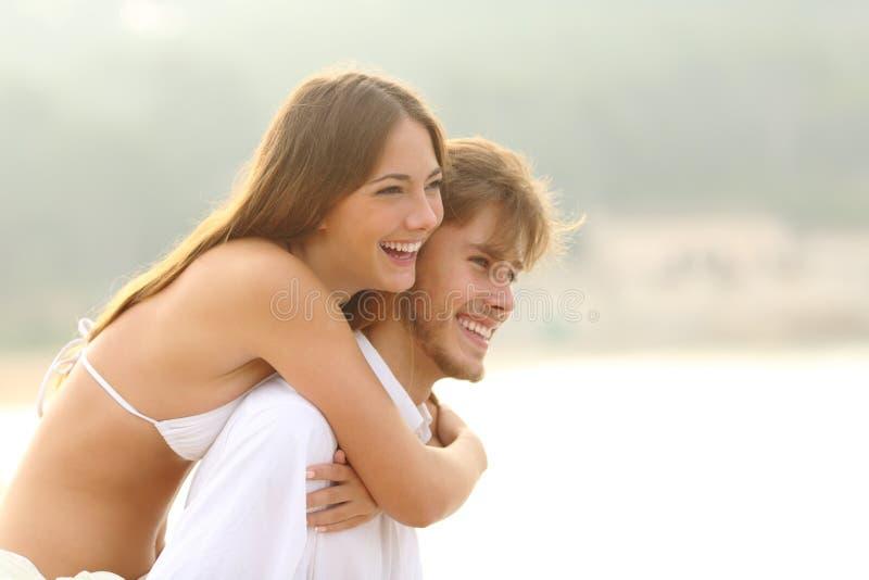 Pares felizes de adolescentes na praia em férias fotos de stock