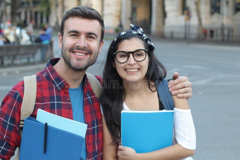 Pares felizes de estudantes universitário fora imagem de stock
