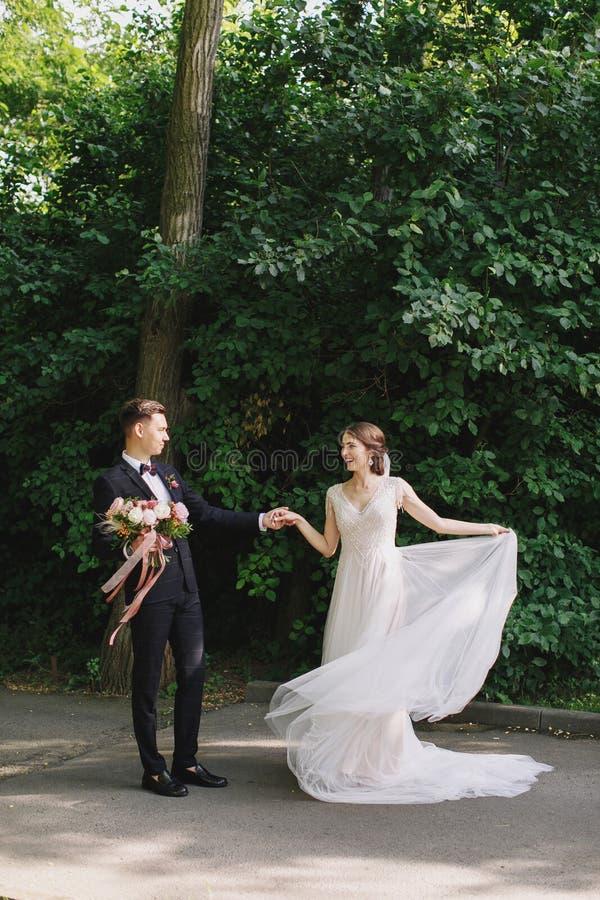 Pares felizes de noivos que andam em um parque Os recém-casados felizes no casamento na natureza esverdeiam o retrato da foto da  fotografia de stock royalty free