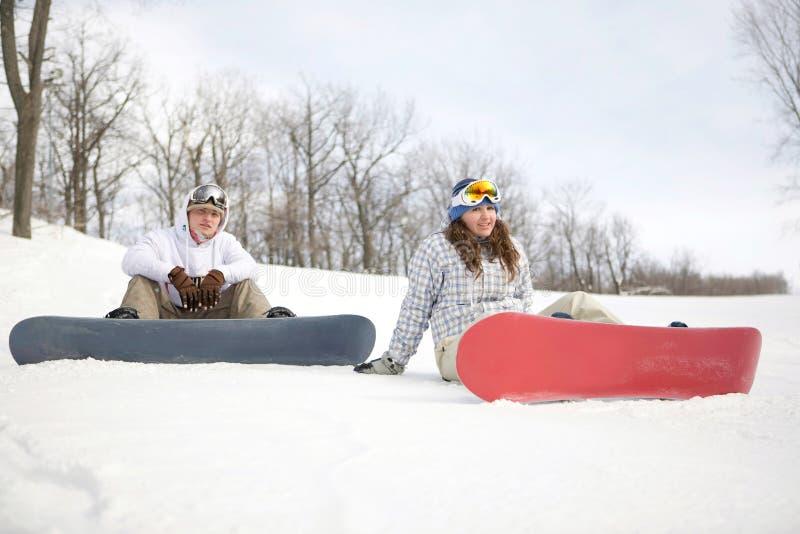 Pares felizes de snowboarders imagem de stock