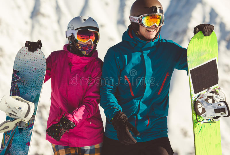 Pares felizes de snowboarders nas montanhas alpinas foto de stock royalty free