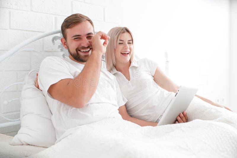 Pares felizes de sorriso com um tablet pc no quarto da cama em casa fotografia de stock royalty free