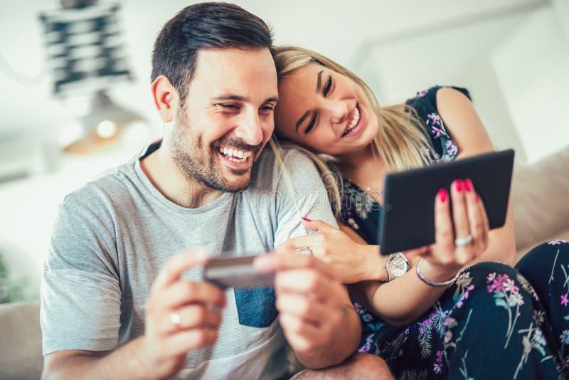 Pares felizes de sorriso dos pares com o computador do PC da tabuleta e o cartão de crédito em casa imagens de stock