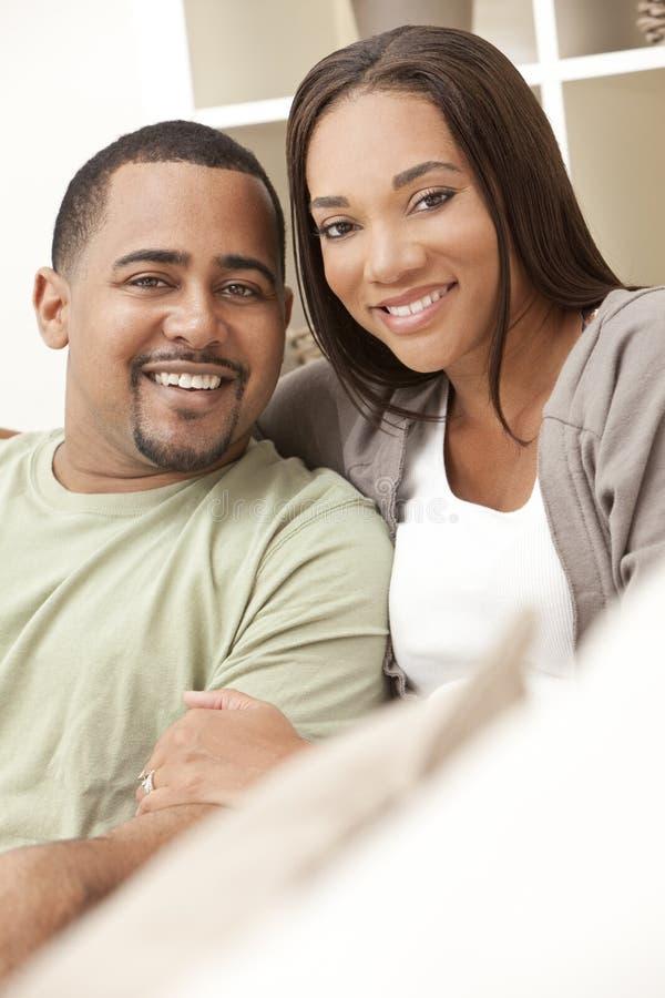 Pares felizes do americano africano que sentam-se em casa fotos de stock