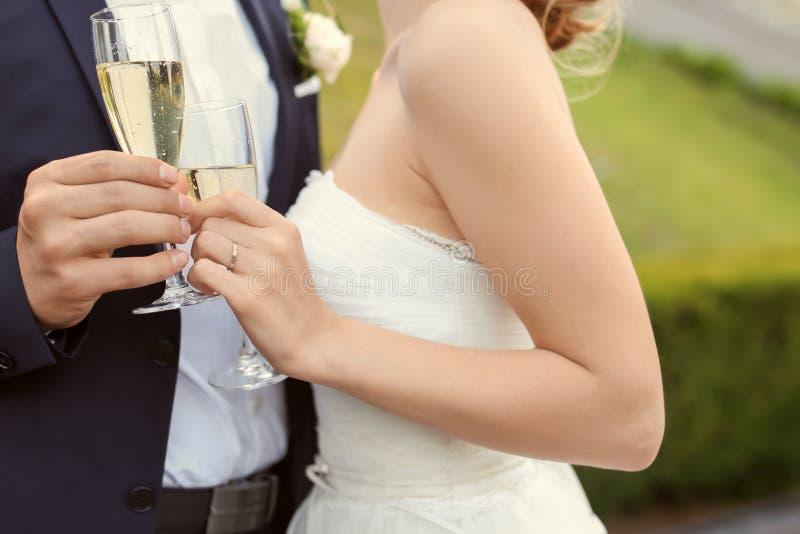 Pares felizes do casamento com vidros do champanhe fora fotos de stock