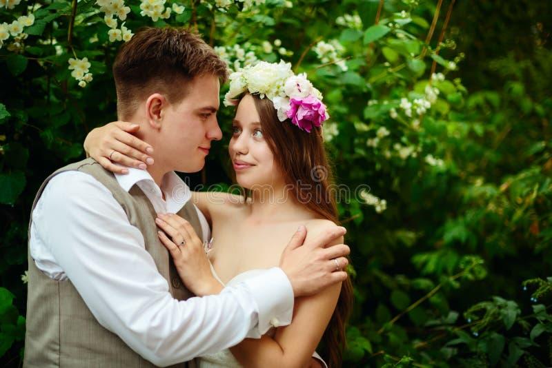 Pares felizes do casamento nas flores imagens de stock royalty free