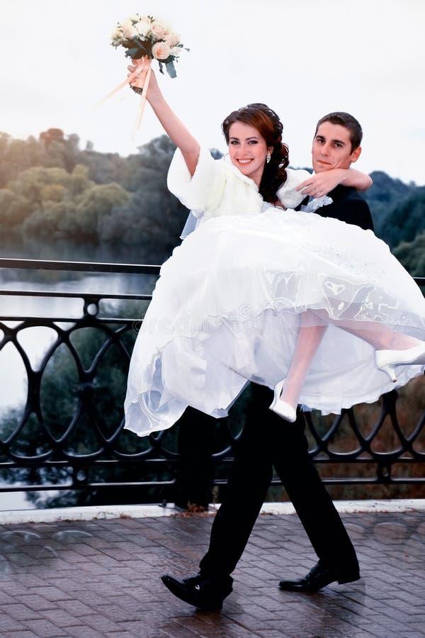Pares felizes do casamento Noivo que leva sua noiva bonita nos braços fotografia de stock