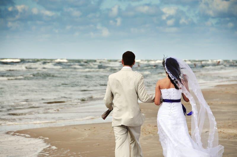 Pares felizes do casamento que andam ao longo do seashore imagem de stock