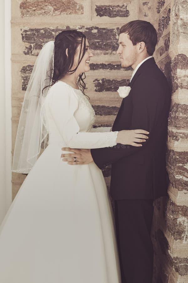 Pares felizes do casamento que estão pela construção de tijolo fotos de stock