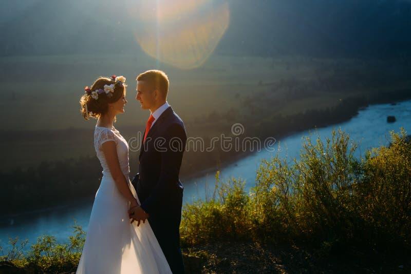 Pares felizes do casamento que ficam sobre a paisagem bonita com montanhas foto de stock royalty free
