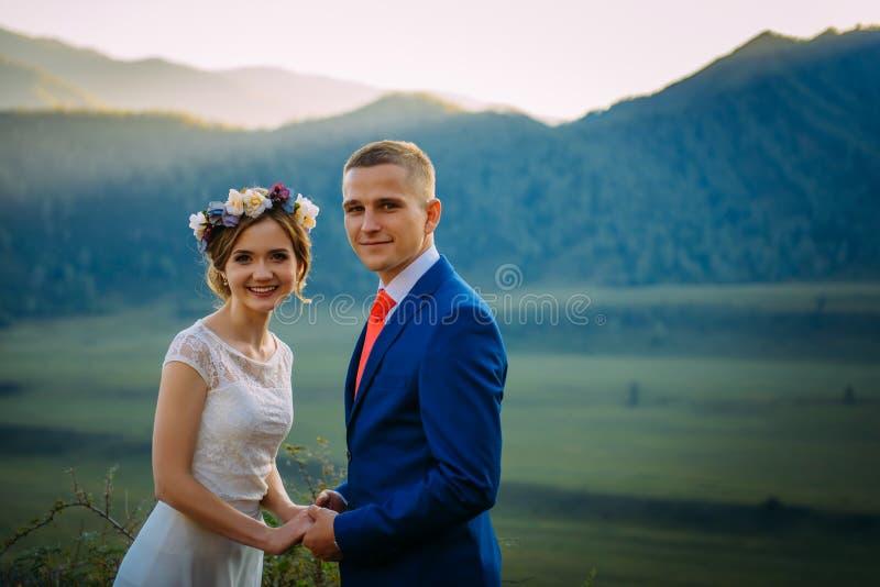 Pares felizes do casamento que ficam sobre a paisagem bonita com montanhas foto de stock