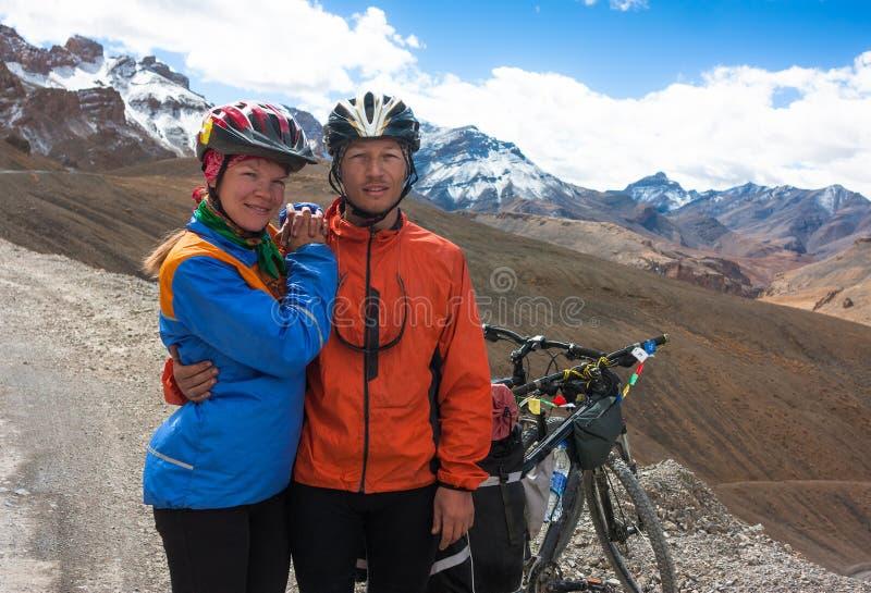 Pares felizes do ciclista que estão na estrada das montanhas fotos de stock royalty free