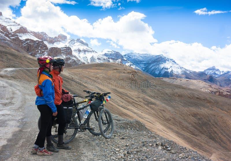 Pares felizes do ciclista que estão na estrada das montanhas imagens de stock royalty free