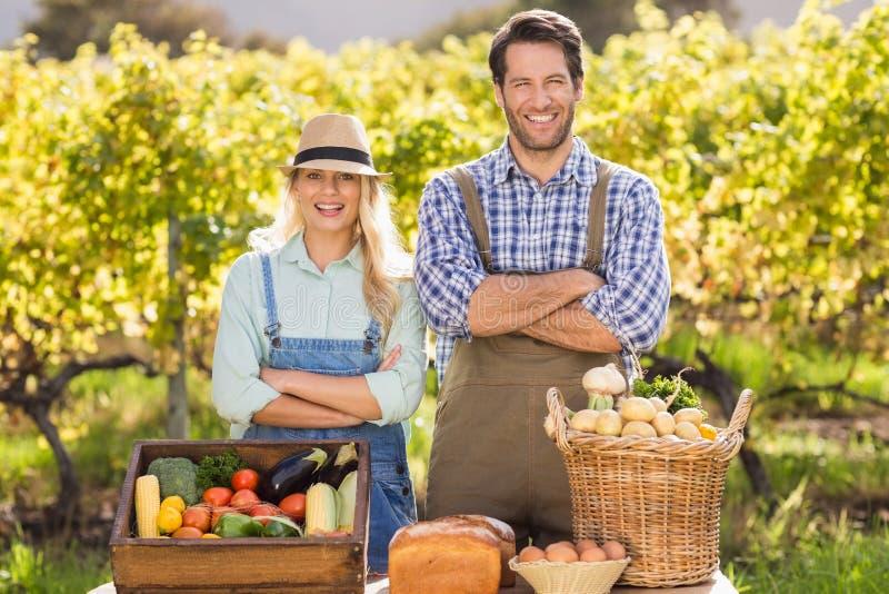 Pares felizes do fazendeiro com os braços cruzados fotos de stock