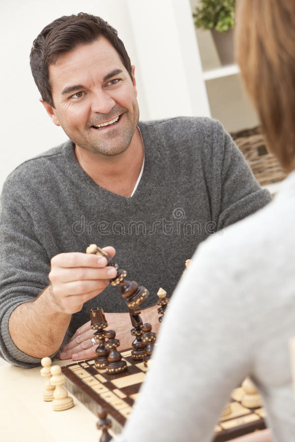 Pares felizes do homem & da mulher que jogam a xadrez imagens de stock
