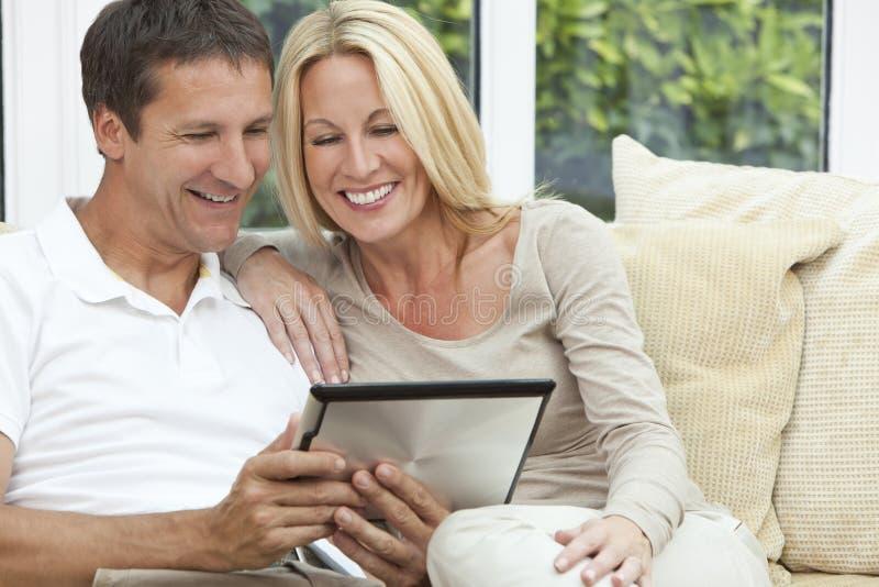 Pares felizes do homem & da mulher usando o computador da tabuleta