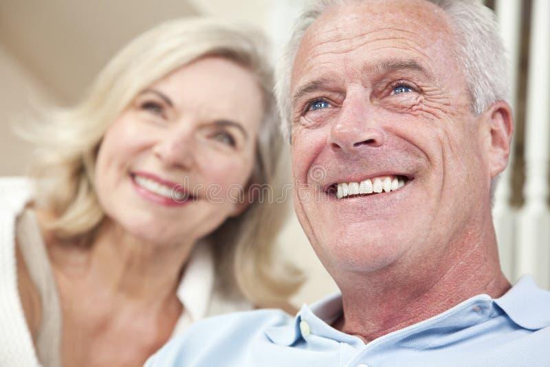 Pares felizes do homem sênior & da mulher que sorriem em casa imagem de stock