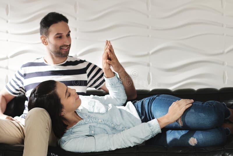 Pares felizes do Latino que guardam as mãos e que sorriem no sofá imagem de stock royalty free