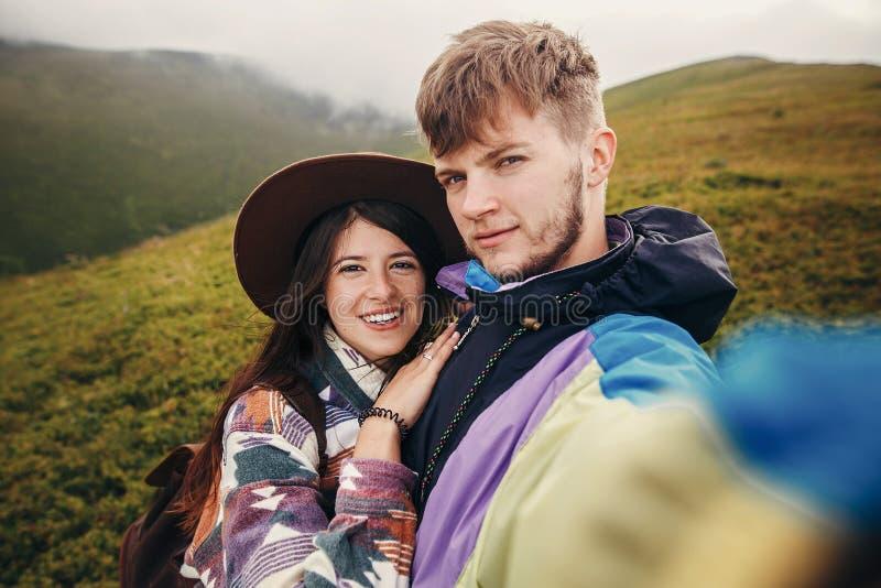 Pares felizes do moderno que fazem o selfie sobre montanhas ensolaradas SU foto de stock