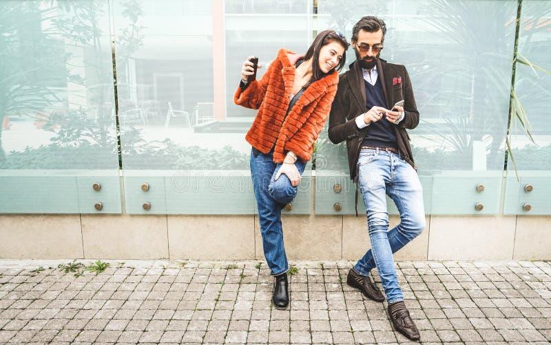 Pares felizes do moderno que têm o divertimento com o telefone esperto móvel no lugar do ar livre - conceito da amizade com conex fotos de stock royalty free