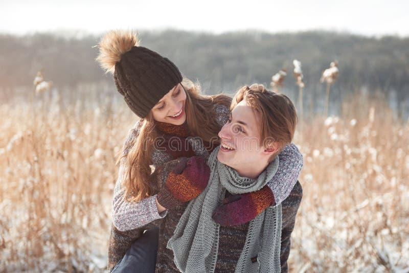 Pares felizes do Natal no abraço do amor na floresta fria do inverno nevado, espaço da cópia, celebração do partido do ano novo,  fotografia de stock royalty free