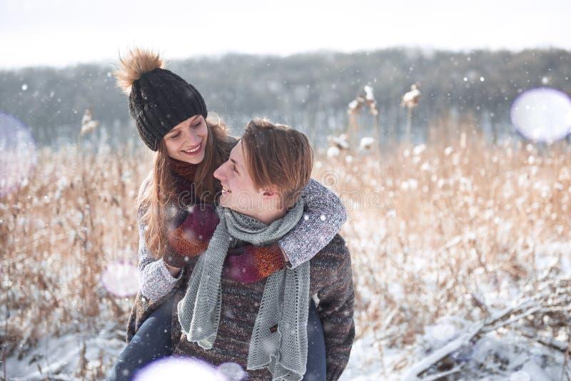 Pares felizes do Natal no abraço do amor na floresta fria do inverno nevado, espaço da cópia, celebração do partido do ano novo,  fotografia de stock