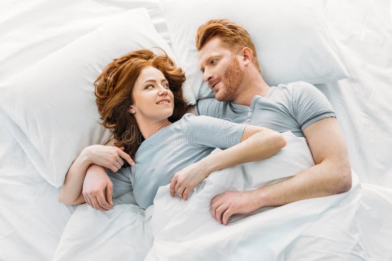 pares felizes do ruivo que sorriem-se ao dormir junto fotografia de stock royalty free