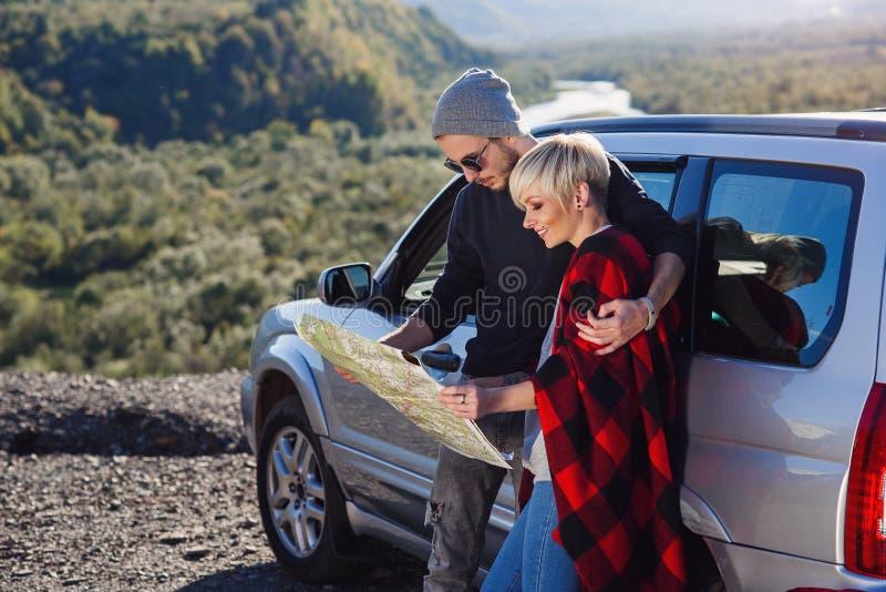 Pares felizes do turista com o mapa do papel perto do carro alugado Jovens na moda que usam o mapa Viagem pelo carro em férias de imagens de stock